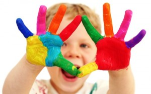 Striking picture of a child holding his brightly-coloured painted hands up to the camera.